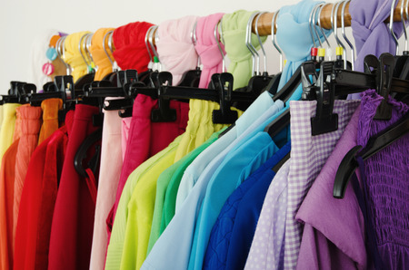 Close up on color coordinated clothes on hangers in a store Detail on all colors clothes hanging on a rack nicely arranged