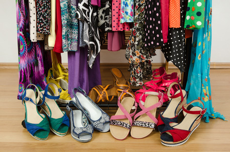 Close up on summer sandals in a wardrobe  Dressing closet with colorful clothes and shoes nicely arranged  photo