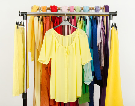 Cute yellow blouse and skirts displayed on a rack  Wardrobe with colorful summer clothes and accessories