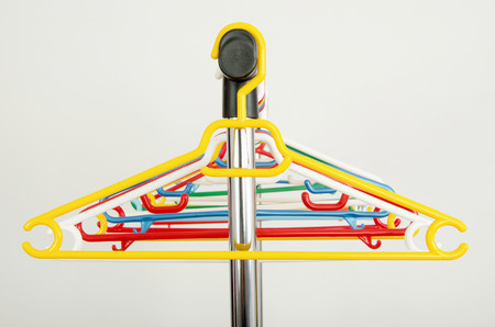 Rack of clothes with empty hangers  Close up on colorful plastic hangers  photo