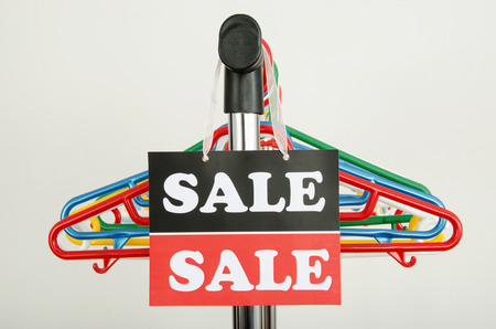 Close up on empty hangers and a big sale sign  Rack of clothes with colorful plastic hangers after a big sale  photo