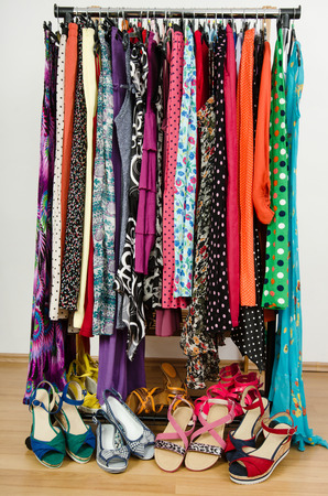 Dressing closet with colorful clothes and shoes nicely arranged on a rack  Summer dresses and sandals in a wardrobe  photo