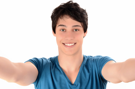 Man smiling with hands reaching out  Happy young man taking a selfie photo