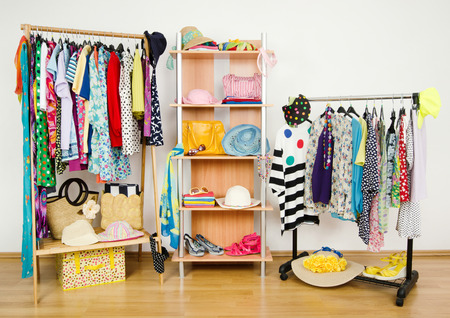 boutique shop: Wardrobe with summer clothes nicely arranged  Dressing closet with colorful clothes and accessories on hangers and a shelf  Stock Photo