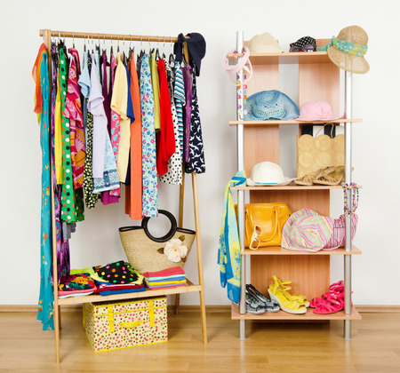Wardrobe with summer clothes nicely arranged  Dressing closet with colorful clothes and accessories on hangers and a shelf  Stock Photo