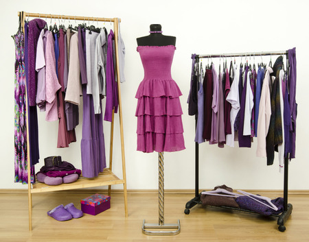 Wardrobe with purple clothes arranged on hangers and a dress on a mannequin  Dressing closet with all shades of violet clothes, shoes and accessories  Stockfoto