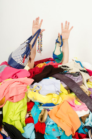 Man hands reaching out from a big pile of clothes and accessories  Man buried under an untidy cluttered woman wardrobe  Man reaching for help from to much woman shopping  Stockfoto