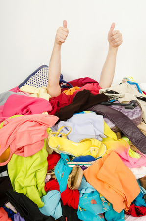 Man hands signing thumbs up reaching out from a big pile of clothes and accessories  Man buried under an untidy cluttered woman wardrobe