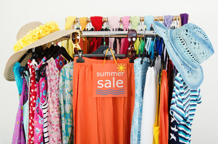 Big sale sign for summer clothes  Clearance rack with colorful summer outfits and accessories displayed on hangers  photo