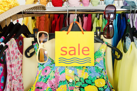 Close up on a big sale sign for summer clothes  Clearance rack with colorful summer outfits and accessories displayed on hangers  photo
