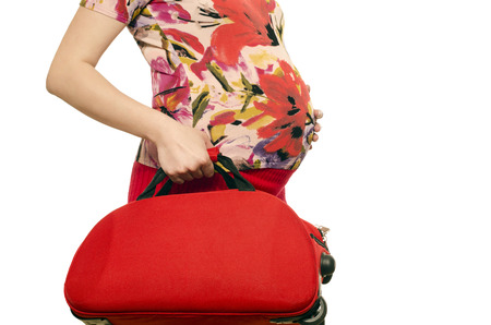 Woman expecting a baby holding a suitcase in her hands isolated on white