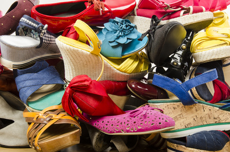 the thrown: Close up on big pile of colorful woman shoes. Untidy stack of shoes thrown on the ground.