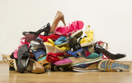 untidy: Big pile of colorful woman shoes. Untidy stack of shoes thrown on the ground.