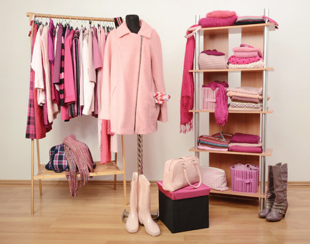 woman closet: Dressing closet with pink clothes arranged on hangers and shelf, a coat on a mannequin. Fall winter wardrobe full of all shades of pink clothes, shoes and accessories. Stock Photo