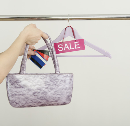 paper hanger: Unrecogniazible woman hand shopping with credit cards on sale. Empty hanger on a rack of clothes with the sale sign.