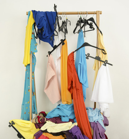 messy clothes: Messy rack of clothes and hangers. Untidy wardrobe with colorful summer outfits and accessories.