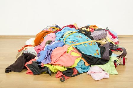 cuarto desordenado: Cierre en una gran pila de ropa y accesorios tirado en el suelo. Armario desordenado desordenado con ropa de colores y accesorios.
