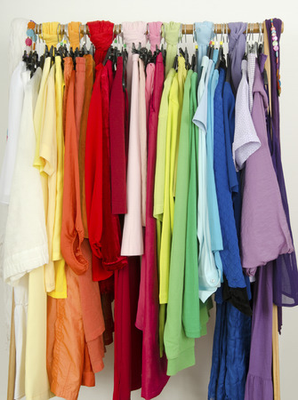 arranged: All colors clothes hanging on a rack nicely arranged. Stock Photo