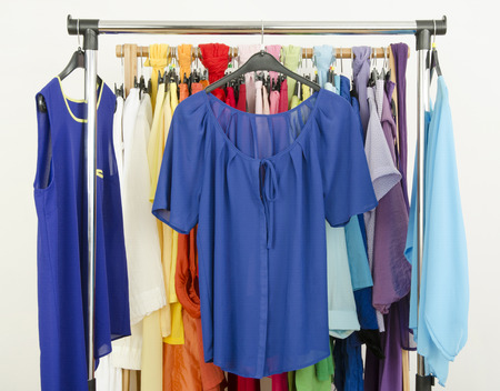 Wardrobe with colorful summer clothes and accessories. Standard-Bild