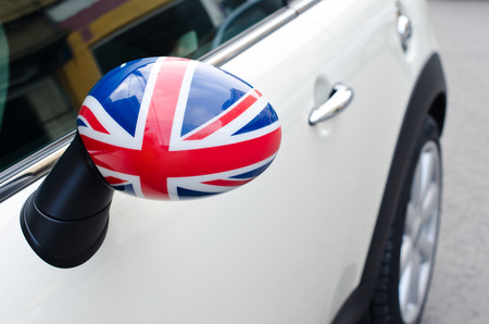 Close up on a side mirror of a car with the UK flag on it. Patriotic driver. England flag. photo