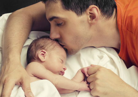 papa: Cher p�re embrassant son b�b� nouveau-n�. P�re embrasser son petit gar�on front tandis que son sommeil et se tenant la main. Amour Parent.