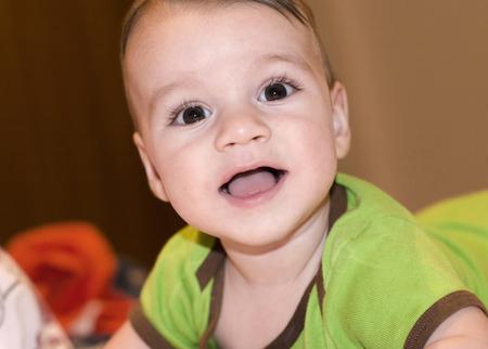 lying on his tummy: Cute happy baby boy smiling. Baby lying on his tummy laughing. Stock Photo