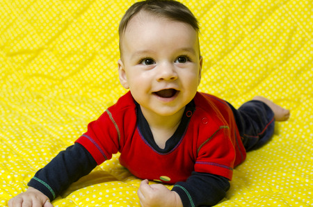 lying on his tummy: Cute happy baby boy. Baby lying on his tummy smiling and looking up. Stock Photo