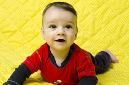 lying on his tummy: Cute baby boy looking up curious. Baby lying on his tummy smiling and looking up.