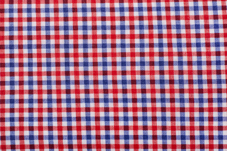 Close up on checkered tablecloth fabric. Red and blue with white tartan square pattern as background. photo