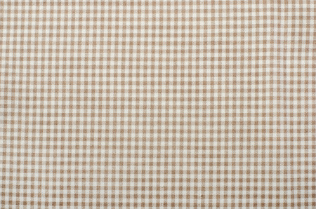 Close up on checkered tablecloth fabric. Brown with white tartan square pattern as background.