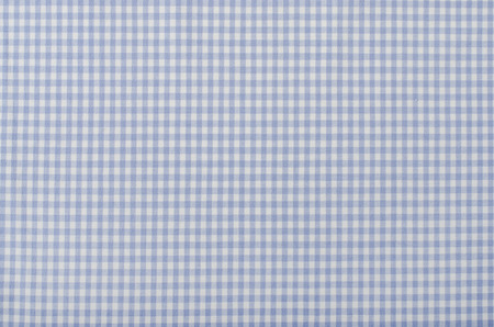 Close up on checkered tablecloth fabric. Blue with white tartan square pattern as background. photo