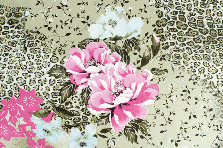 Floral and cheetah pattern on fabric. Brown leopard pattern with pink roses. Spotted animal print as background. Chabby chic material. Standard-Bild