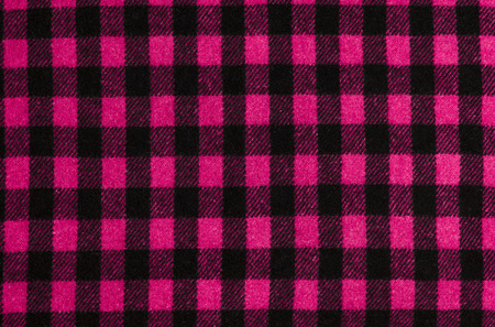 Closeup on checkered tablecloth wool fabric. Magenta pink with black gingham square pattern as background. photo