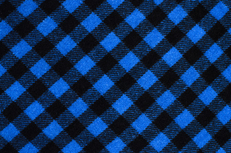 Closeup on checkered tablecloth wool fabric. Blue with black gingham square pattern as background. photo