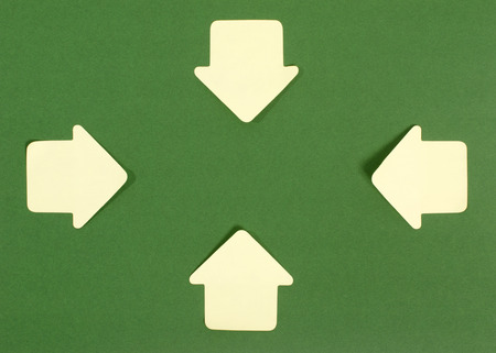 inward: Paper arrows pointing inward. Yellow sticky notes arrows on green background facing in.