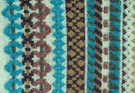 close knit: Close up on knit woolen texture. Blue and brown geometric shapes background. Stock Photo