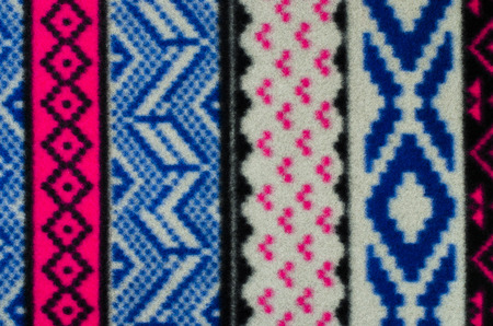 close knit: Close up on knit woolen texture. Blue, grey and pink geometric shapes pattern as a background.