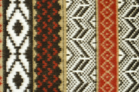 close knit: Close up on knit woolen texture. Brown and red geometric shapes pattern as a background.