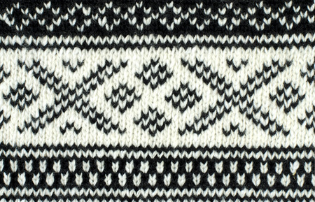 close knit: Close up on knit woolen texture. Black and white winter shapes pattern as a background.