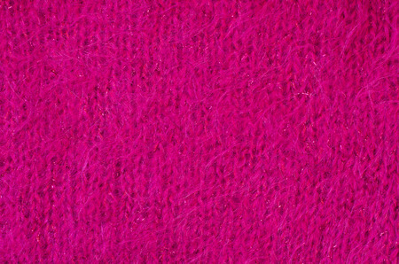 close knit: Close up on knit woolen fur texture. Magenta pink fluffy woven thread sweater as a background. Stock Photo