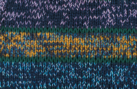 close knit: Close up on knit woolen texture. Green, yellow and blue woven thread sweater as a background.