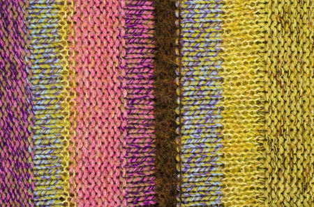 close knit: Close up on knit woolen texture. Pink and yellow woven thread sweater as a background. Stock Photo