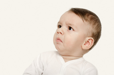 Cute baby boy looking up upset. Baby looking disgusted. Isolated on white. Stockfoto