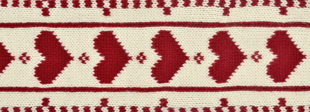 close knit: Close up on knit woolen texture. Red heart pattern as a background.