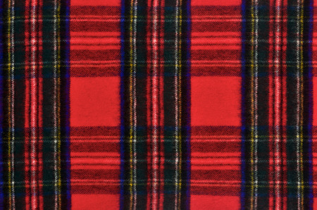 red plaid: Scottish tartan pattern. Red and black wool plaid print as background. Symmetric square pattern. Stock Photo