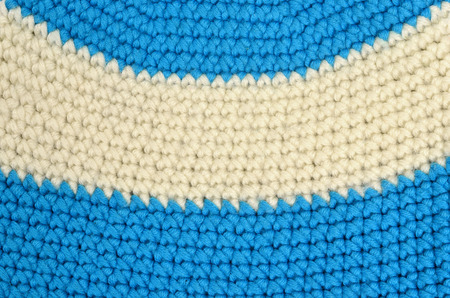 close knit: Close up on knit woolen texture. Blue and white woven thread as a background.