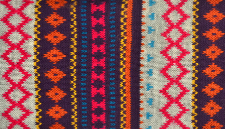 close knit: Close up on knit woolen texture. Colorful geometric shapes pattern as a background. Stock Photo