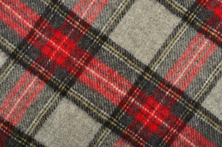 red plaid: Scottish tartan pattern. Red and grey wool plaid print as background. Rhombus pattern.