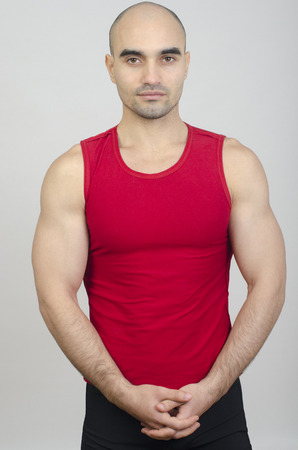 tank top: Portrait of a handsome bald man.  Fit athletic bodybuilder wearing a red tank top.