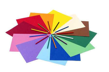 Color pencils on paper. All colors pencils arranged in a circle and rainbow color paper isolated on white background.